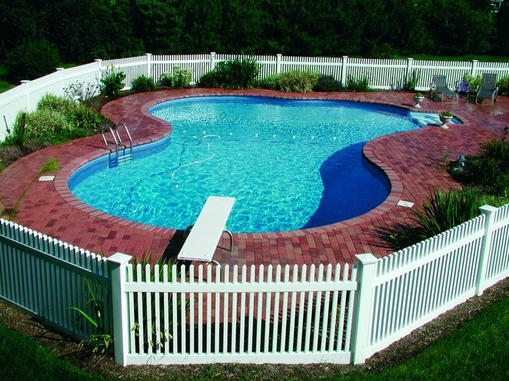 Idyllic freeform fiberglass pool complete with diving board and picket fence
