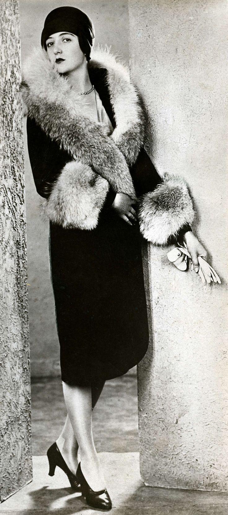 Mode toen en nu. De wintermantel voor 1928 : zwart fluweel met een vossenbont. Foto geplaatst bij artikel in Het Leven: Dameskleding van 1914 en nu: wat is beter.