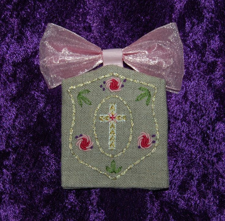 "Escapulario; Pin back brooch; shield design with ribbon cross, bullion roses, French knots, and pink bow tie; natural linen; 2.25"" wide by 2.50"" long, plus ribbon; 3.25.17"