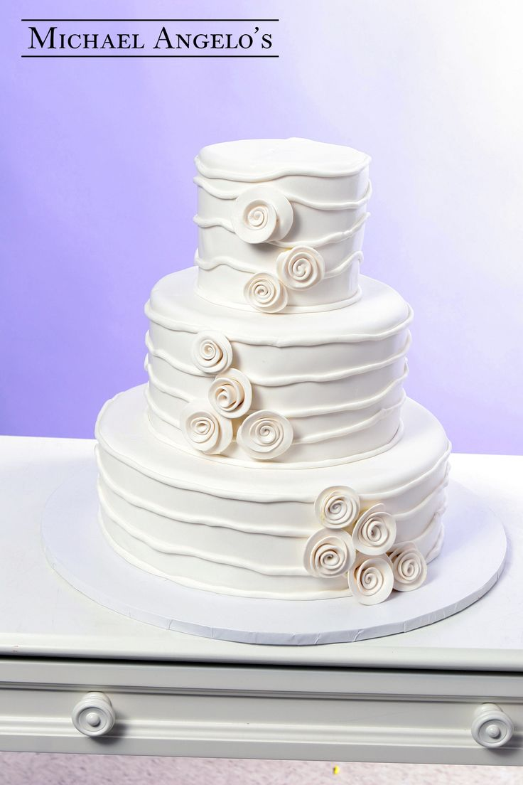 Rolled Roses #41Modern  This wedding cake is iced in buttercream and then accented with rolled fondant to create this modern look. The rolled rose clusters add a beautiful touch to this design