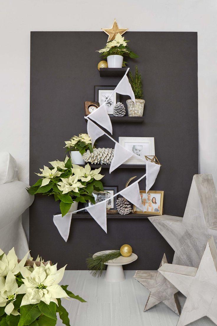 Eine einfache, nach Maß geschnittene schwarze MDF-Platte und passende Regalböden aus dem Baumarkt werden zusammen montiert und mit cremefarbenen Poinsettien, Familienfotos und Deko-Sternen geschmückt.