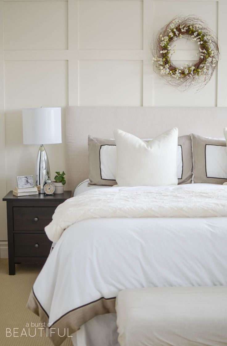 A Neutral Farmhouse Bedroom Welcomes Spring With Classic White Bedding Grey Wingback Chair And