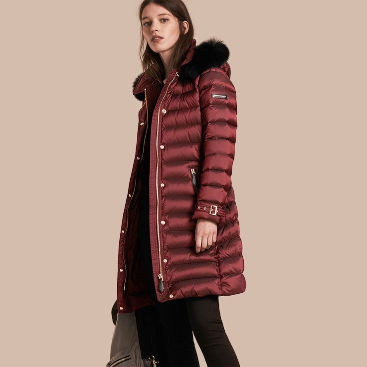 A cold-weather Burberry coat in Burgundy to accommodate changing temperatures, with down insulation and a drawcord hood.