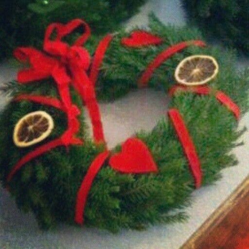Julkrans i granris, pyntad med torkade apelsinskivor, filthjärtan och rött band.