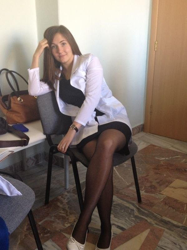 Sexy Brunette Casually Poses With Her Legs Crossed Wearing ...