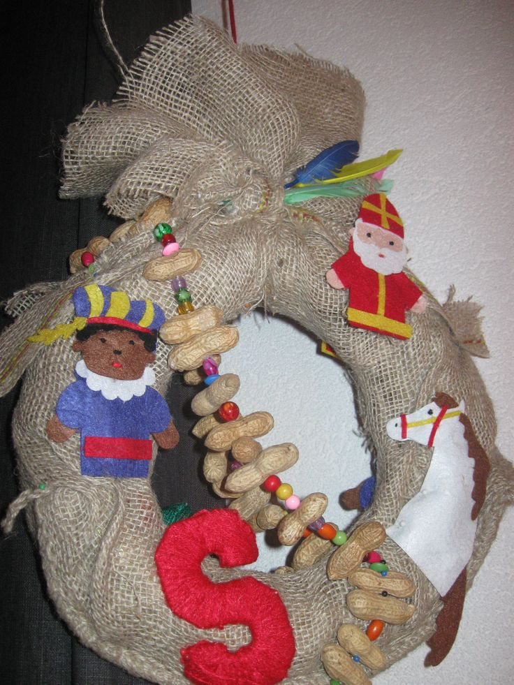 Sinterklaas krans gemaakt van strokrans, jute, vingerpoppjes, pinda's, veren en kralen