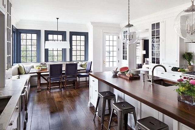 Kitchen. Open Kitchen design with custom white cabinets and custom banquette in breakast room. Pendants are the