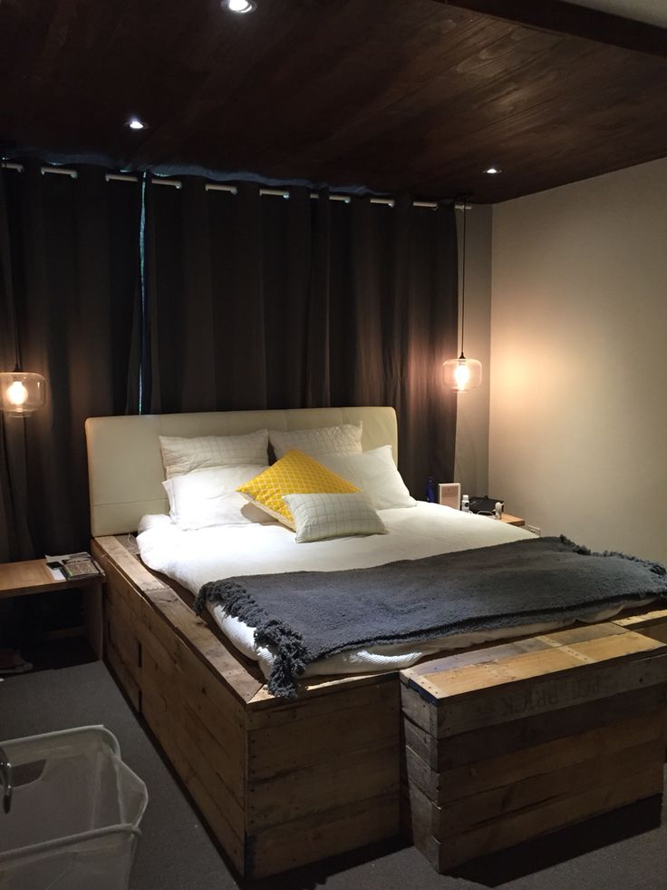 Timber bed made from old pallets. Timber bulkhead made from finished pine and stained. Edison bulbs and bed side tables finish the ensemble