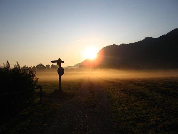 Die Welt von oben: Kampenwand und Kaiserwinkel (Österreich). Chiemgau-Ausflug, Teil 3 Am dritten Tag wollen wir wieder am Himmel kratzen. Schon in aller Frühe spaziere ich zum nahe an der Pension gelegenen Badesee, wobei ich andächtig den über dem Wiesennebel schwebenden Sonnenball betrachte (und fotografiere). Nach dem reichhaltigen Frühstück geht es per Auto nach Aschau, wo sich die Talstation der Kampenwandbahn befindet.