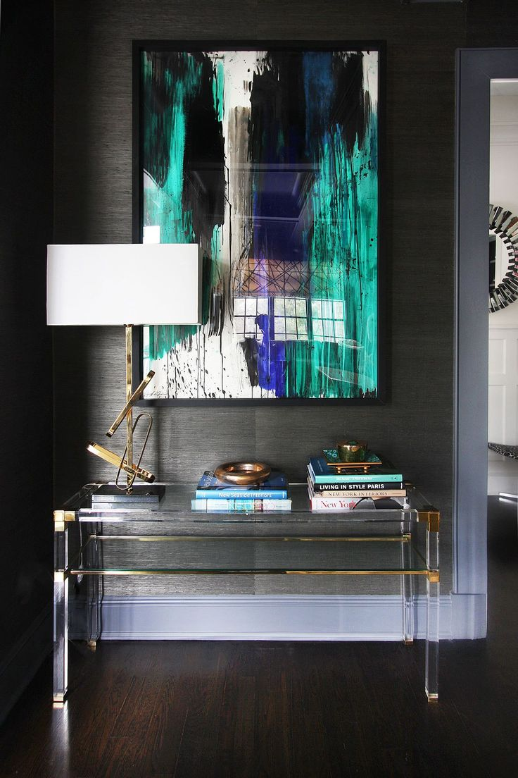Dramatic vignette of abstract art, lucite & polished brass against a pewter grasscloth backdrop