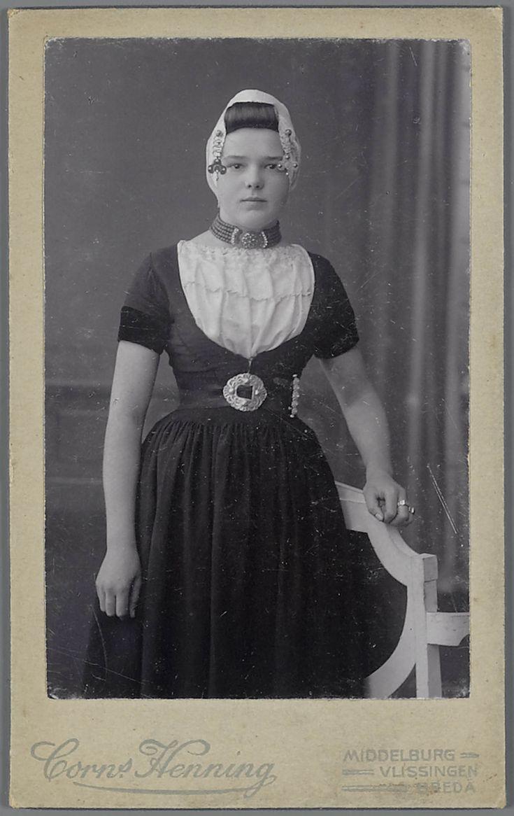 Jonge vrouw in Walcherse streekdracht. De vrouw is gekleed in haar zondagse dracht. Aan de gouden 'krullen' (oorijzeruiteinden) hangen klaverbladvormige gouden oorijzerhangers. Rond haar middel draagt ze een ceintuur, met een sluiting welke gemaakt is van een hergebruikte zilveren schoengesp. 1900-1910 #Zeeland #Walcheren