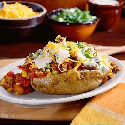 Chili-Topped Potatoes      This recipe packs meat, corn, beans, and onions into a hearty spud. Finish this one-dish meal off with your favorite potato                                         toppers.