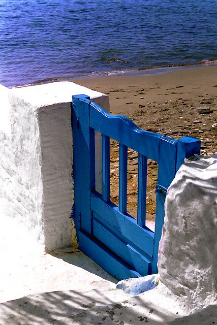 Tiny blue wooden gate overlooking an empty beach. Isternia Beach. Tinos Island, Cyclades Islands. Greece.