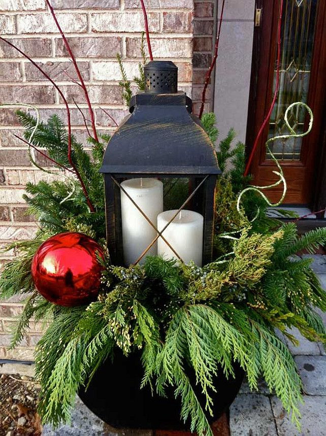 Winter Urn. Christmas urn decor. Christmas planter urn decor. Christmas planter urn with large lantern, red Christmas balls, branches and evergreen. #ChristmasPlanter #ChristmasUrn Via Ringers Landscaping.