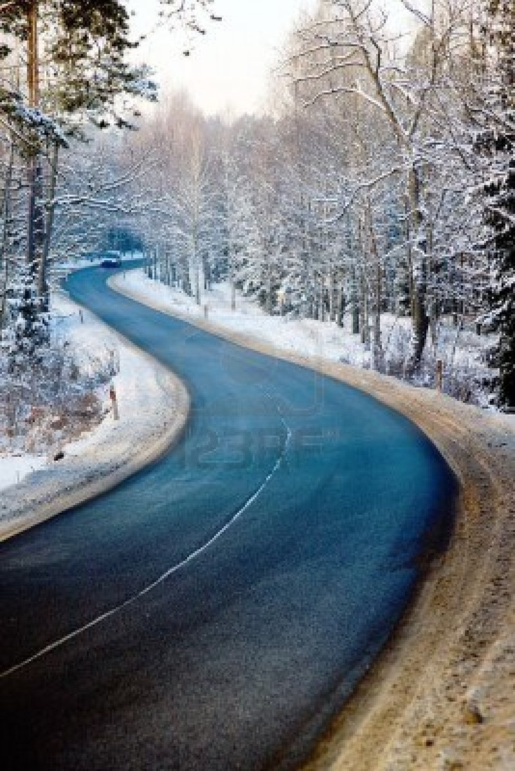 Road in forest in winter and a distant car