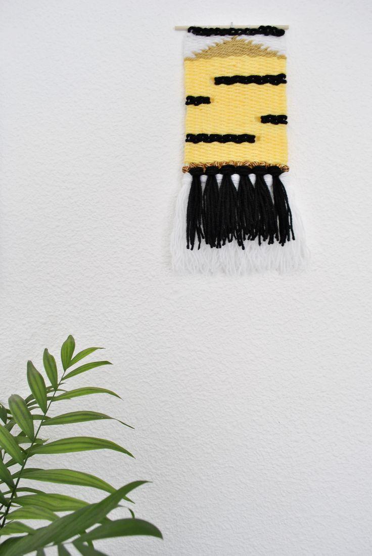Hecho totalmente a mano con amor ❤ y en un ambiente sin humos.Ideal para colgar en la pared y formar parte de la decoración en casa. Tejido en una unión de colores y lanas, en amarillo, blanco y negro, con abalorios animal print de madera.El amarillo está pegando fuerte, así que es una opción segura!Sujeto en una varilla redonda de madera natural y con hilo egipcio para poder colgarlo de ahí si lo prefieres.Dimensiones - Largo: 33cm con flecos / 21cm sin los flecos...