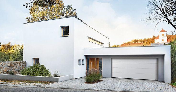 Passend auf die Architektur des Gebäudes abgestimmtes Sektionaltor mit Großlamelle und glatter Oberfläche in Weiß.