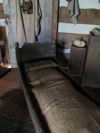 Early hired man's bed in original grungy brown paint; all pegged. Best grungy surface and wear.  $ 1095.00