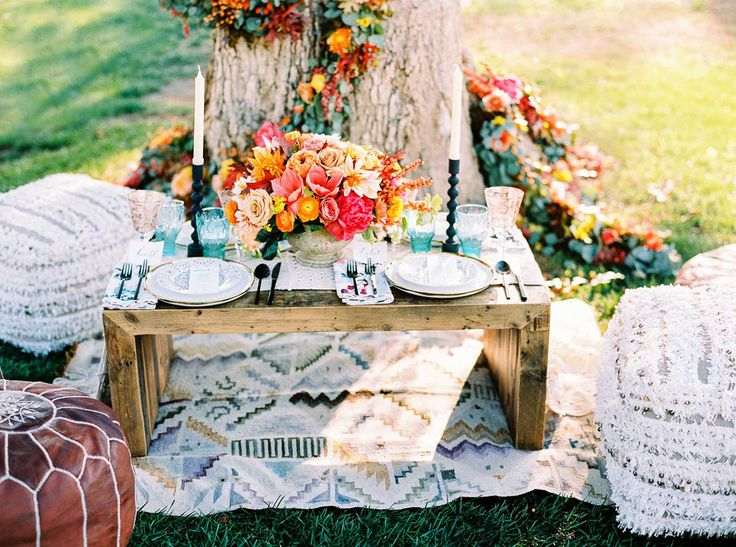 colorful fall tablescape with pops of turquoise, coral and orange. Moroccan poufs used instead of chairs