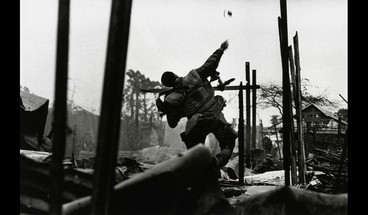 A US Marine throwing a grenade in Hue, Vietnam (February 1968). Don McCullin.