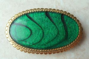 An oval green enamel and black striped vintage brooch manufactured by W A P Watson, under the Exquisite brand.  The brooch is formed in an oval shape, with a central inlay of green enamel and black tiger style stripes set in a ornate gold tone metal frame.  Circa 1960's - 70's.