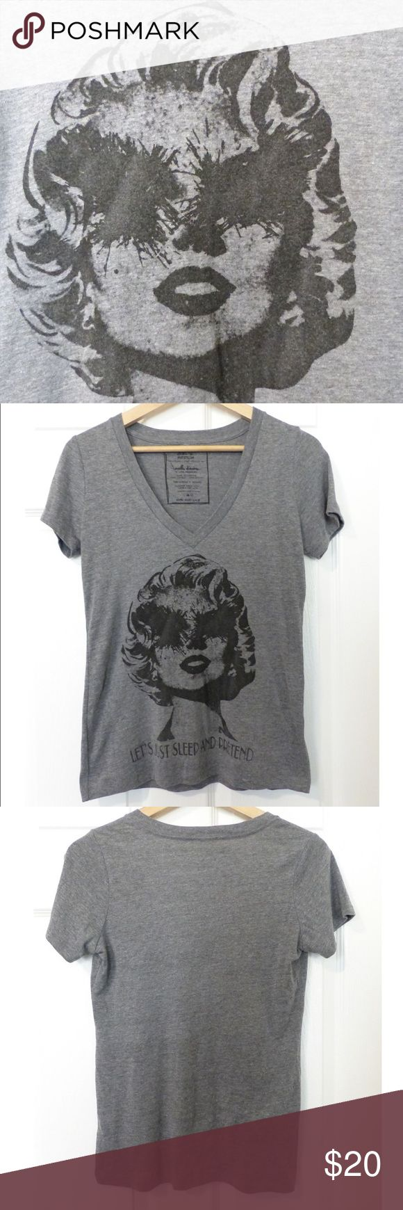 "HIPS & HAIR Marilyn Monroe Eyeless Graphic Tee M Worn once. Unique women's graphic V-neck t-shirt with a morbid twist to the Iconic Marilyn Monroe face with scratched or removed eyes graphic printed with ""Let's Just Sleep and Pretend"" to your wardrobe. Marilyn Monroe fans, this one's for you.  Size: Medium -   Measurements:  Shoulder-to-shoulder: 15 Armpit-to-Armpit: 17 1/2 Full Bust: 35 Top to bottom: 25 1/2 Side Seams: 18 1/2 Sleeve Length: 7 Sleeve Full Opening: 12 1/2 Hem Full Opening…"