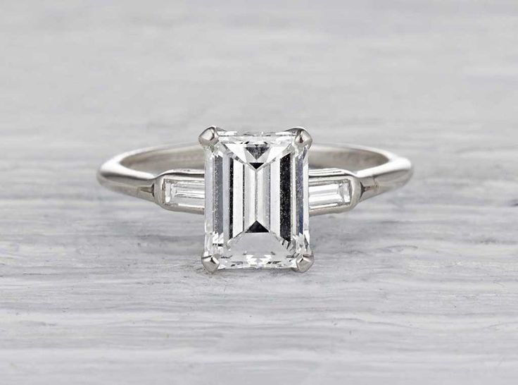 Antique Art Deco engagement ring made in platinum and centered with a GIA certified 1.92 carat emerald cut diamond with E color and VVS1 clarity. Accented with two baguette cut diamonds. Circa 1932.