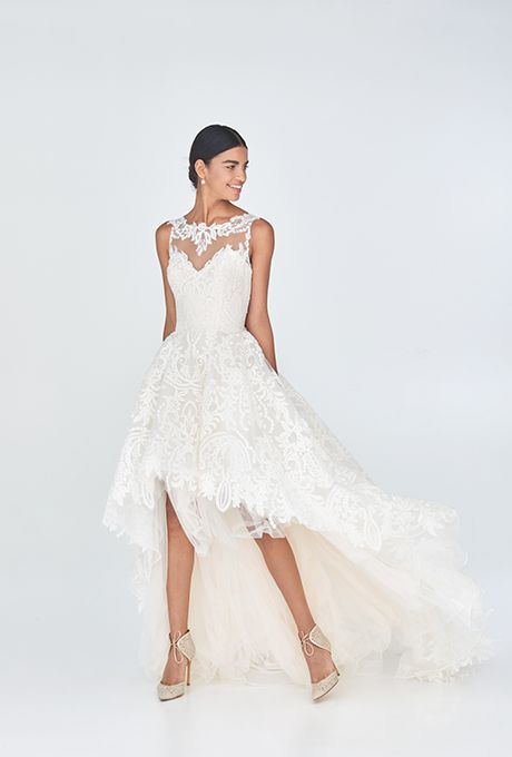 Brides.com: . Justin Alexander chose full on drama for this version of high-low. Tulle, lace, and embroidery make a big statement.