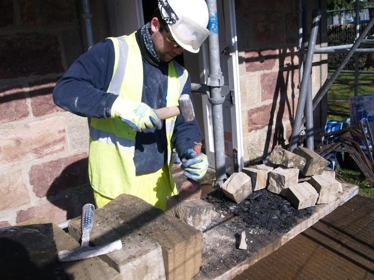 Preparing sandstone regular sized sandstone blocks ready for building up wall heads.