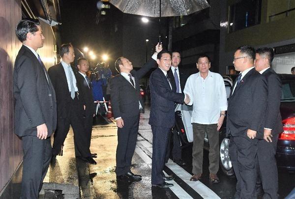 岸田文雄外相(中央)との夕食会会場に到着し、握手を交わすフィリピンのドゥテルテ大統領(右から3人目)=10月25日午後、東京都中央区(宮崎瑞穂撮影)