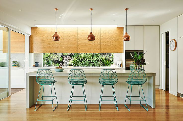 Built by Wilson Gorgeous kitchen with glass window splash back, copper pendants and aqua stools for a colour pop