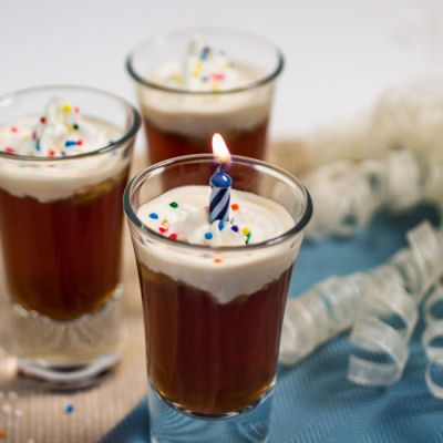 Birthday Cake Shots INGREDIENTS  1 part white cake vodka, chilled  1 part dark chocolate vodka, chilled  dollop of whipped cream  sprinkles (optional)  candle, cut to 3/4″ length  DIRECTIONS  Mix equal parts liquor in a shot glass. Use a piping bag to pipe the whipped cream on top of the shot. Dot sprinkles on top of the whipped cream. Insert candle in cream and light. MAKE A WISH AND SHOOT!