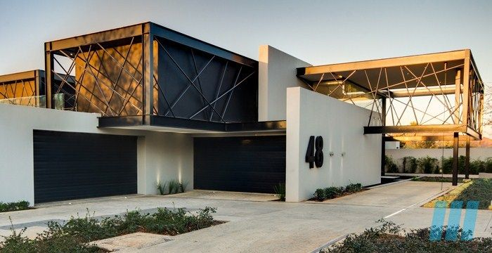 FutureSpaces - House Ber, Carlsworld, Midrand, South Africa. Rectangular in form, the double volume spaces embraces the open plan of this home, while the bold steel bars make a point of being noticed.