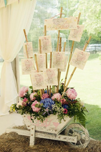 Hosting a garden wedding? Display place cards in a repurposed wheelbarrow. Use a styrofoam block, wooden dowels, and flowers to create this floral display.