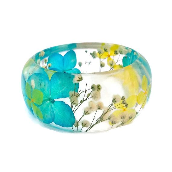This handmade bangle bracelet features pressed blue and yellow hydrangea flowers and white babys breath that are encased in resin. It is a chunky bangle with a curved profile; thicker in the center and tapering on the sides. My work features dried botanicals in contemporary resin