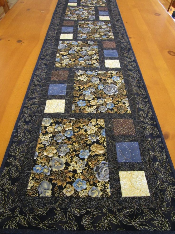The flowers are gorgeous in this table runner. The background is black and most of the fabric has black in it. The little squares are gray, brown and gold. All of the prints have a bit of metallic gol..