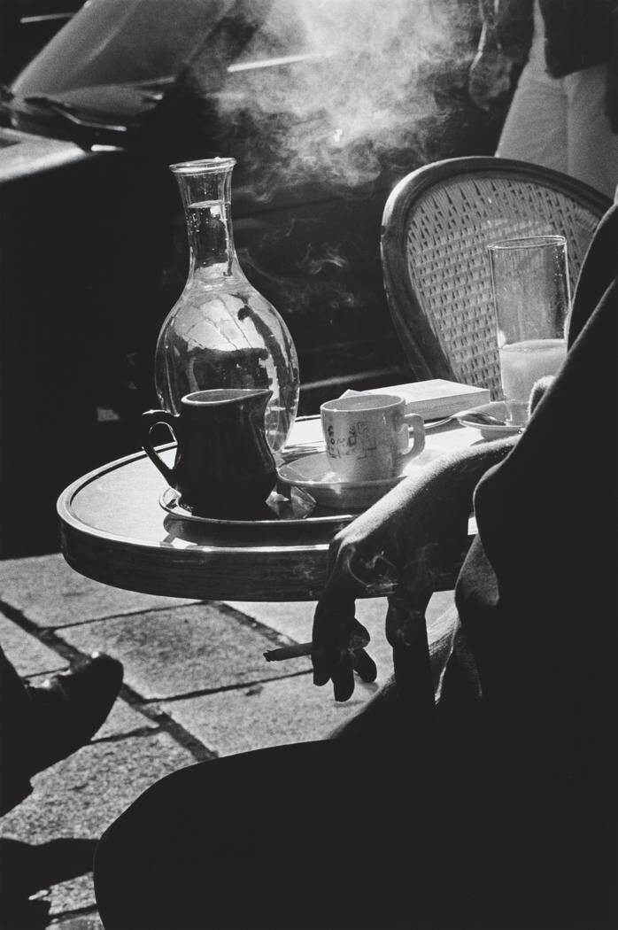 """"""" Ralph Gibson Cafe, Paris, 1986 [person smoking in front of table with coffee cup, water glass and jug, and creamer holder upon in, chair in background] gelatin silver print. """""""