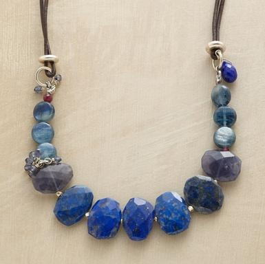 "KITH AND KIN NECKLACE -- Our family of blues includes lapis, kyanite and iolite; a tiny ruby and rhodolite garnet inherited the red gene. Double leather strand; sterling silver button. Handcrafted exclusive. 18""L."