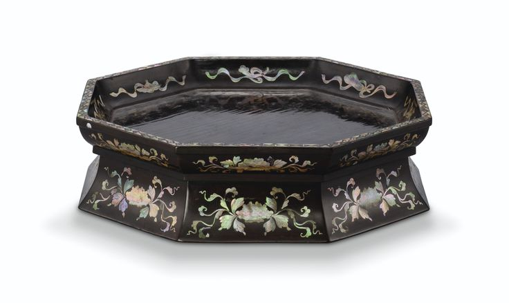 A MOTHER-OF-PEARL INLAID BLACK LACQUER FOOTED TRAY RYUKYU KINGDOM, 18TH CENTURY of octagonal form with shallow rounded sides and a flanged rim, raised on a flared base of conforming section, inlaid in iridescent sections of mother-of-pearl, the exterior walls with foliate peony blossoms, the cavetto with eight beribboned auspicious treasures, all finely detailed with incisions, the rim decorated with a border of checkered lozenges enclosing florets, the interior and the base lacquered in…