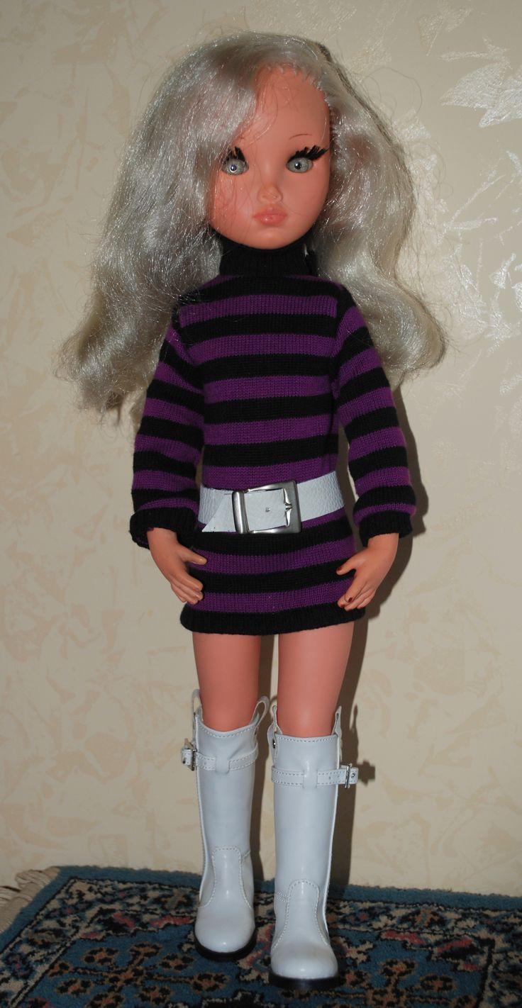 Sylvie con miniabito a righe nero-viola  e cinturone e stivali bianchi coordinati