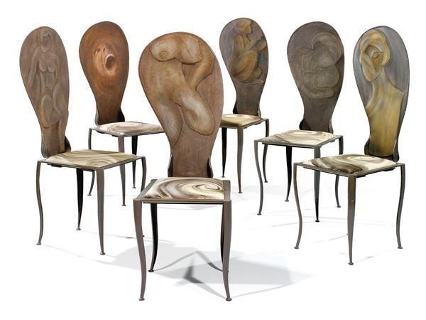 """Marika CARNITI BOLLEA (Née en 1933) Suite de six chaises """"Aliena"""", circa 2000, structure en fer forgé main, chaque dossier est orné, sur les deux faces, d'une femme en bas-relief, dans différentes postures, chaque face étant traitée avec un matériau différent, mousse ou granité, créant ainsi une émotion différente. Le dossier est tendu d'un tulle métallique, galette d'assise mobile tendue d'un tissu peint par l'artiste. Plaque de l'artiste."""