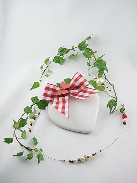 Dekorativer Fensterhänger aus einem  Keramikherz in Weiß und Rot mit Schmuckschnur.   Das Herz hat eine rot-weiß karierte Satinschleife und eine ...