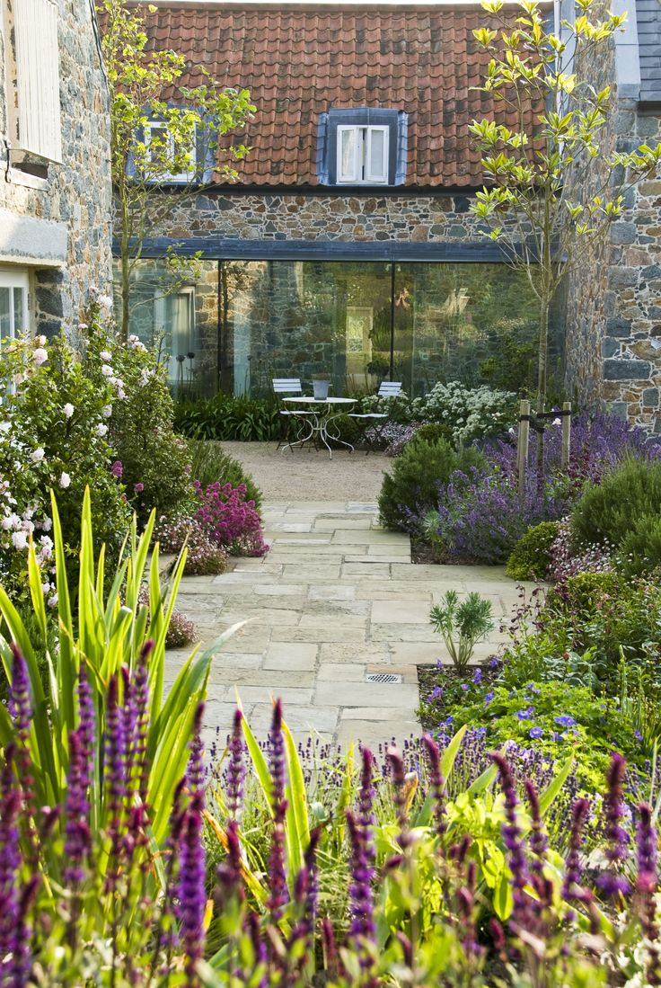 Le Haut, Guernsey  The garden surrounds a refurbished and extended traditional granite house, set among a network of high-banked lanes. The new design keeps the garden inward looking to provide shelter but with glimpses out at key points to link with the surrounding landscape. Terraces and seating spaces are linked by weathered stone paths through granite retaining walls and planted banks. Designer Debbie Roberts MSGD - SGD2014 = Society of Garden Designers