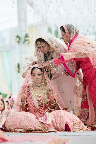 Bride photo with her mother, brides mother adjusting brides outfit, pastel pink dupatta on bride, baby pink lehenga , soft pink lehenga , large nosering , vintage jewellery