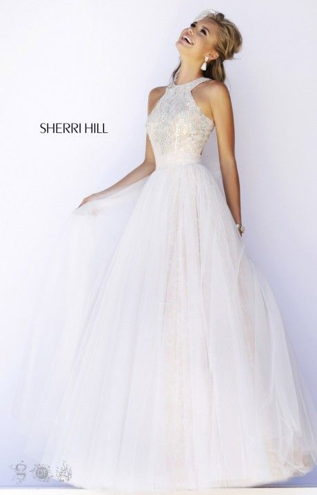Sherri Hill 32218 displays sweet southern elegance like no other! This ballgown has a high neckline and a beaded bust that we simply love for quinceaneras, pageants, prom and more. The full tulle ballgown skirt features a lace like design adding to the cinderella presence. The high neckline wraps around the neck and joins an open cut out in the back but not to worry, this dress doesn't show off too much!