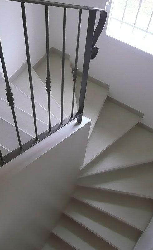 Escalier béton teinté ton pierre 2/4 tournant, mur d'échiffre plâtrée avec garde corps métallique.