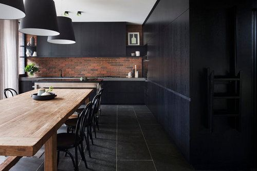 Modern, sleek black cabinets paired with a natural wood table warms up such a dark, minimalist space