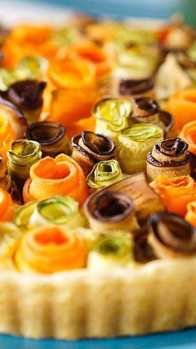 Receita com instruções em vídeo: Essa linda torta de flores de legumes é de comer com os olhos! Ingredientes: 300g de farinha de trigo, 160g manteiga, Sal, 7 colheres de sopa de água gelada, 1 abobrinha italiana , 1 berinjela, 2 cenouras, 2 ovos, ½ xícara de creme de leite fresco, 400g de ricota fresca triturada, 150g de queijo parmesão ralado, Pimenta do reino