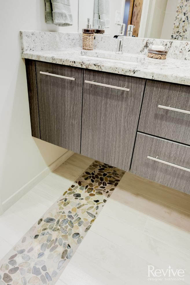 The stony accent seen in the bath area carries through the entire space, accenting the color palette throughout.