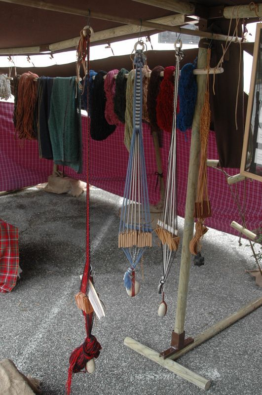photo image d' une animation artisanale filage laine et fibres naturelles lors d' une fête gaulois et romains - organiser avec des Animation de vieux métiers d' artisan - Metier à tisser à plaquettes pour faire du tissage de passementerie, galon, ceinture et ruban celte et romain